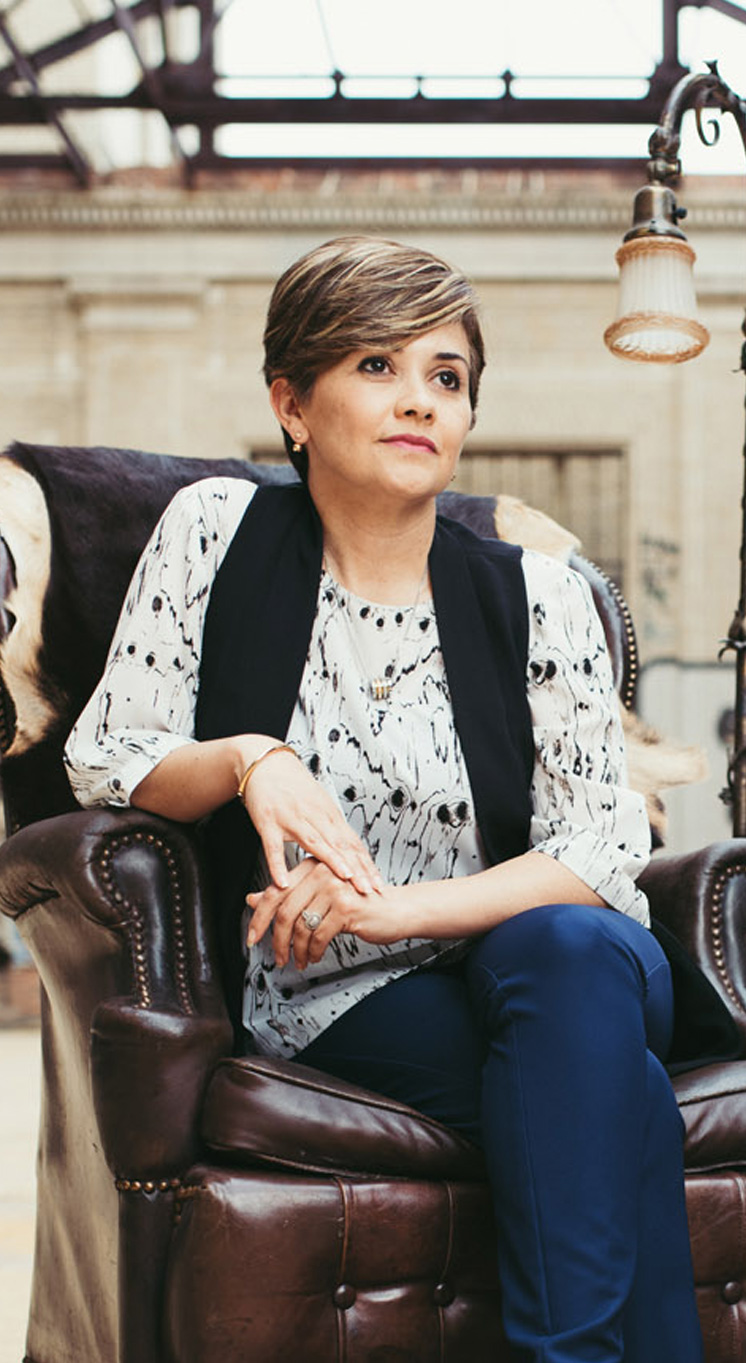 Maricela Hernandez sits in a leather chair looking calm and confident.