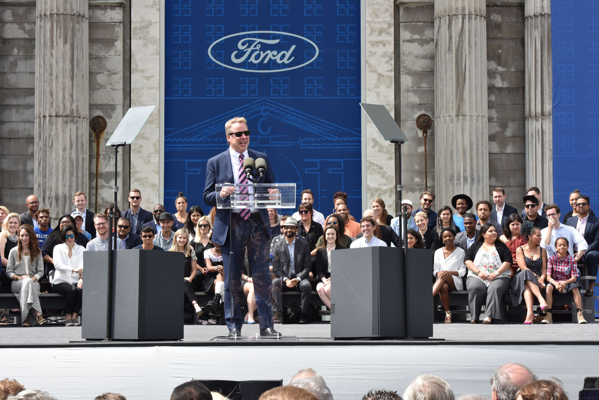 Bill Ford speaking in front of Michigan Central to an audience.