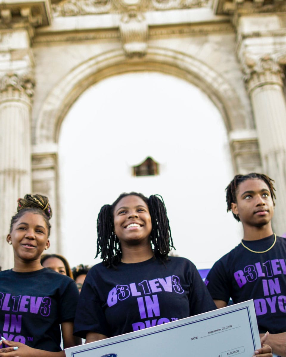 Three Ford Track community youth stand proudly in front of Michigan Central Station architecture.