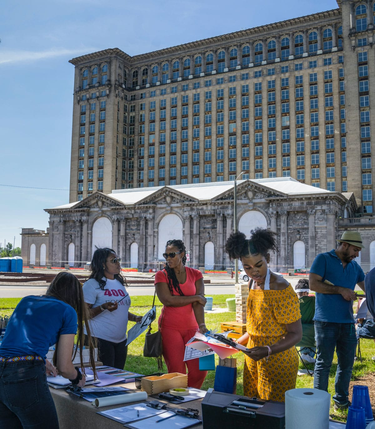 Neighborhood people gather in front of Michigan Central Station for an event on a sunny day.